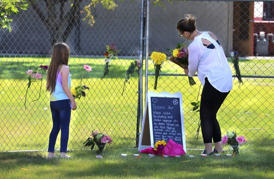 Mindy Marsh and her daughter, Taryn, place a bouquet of flowers at the memorial site at Hamilton's Daly Elementary for 9-year-old Robert Leonardi who was killed Sunday in a hit-and-run crash as he attempted to cross Golf Course Road with his scooter. Leonardi would have entered the third grade at the elementary school this fall.