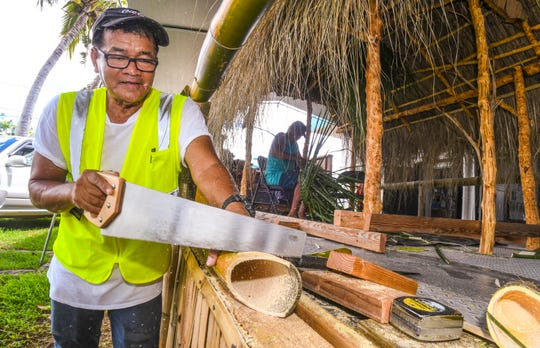 Saw dust flies as carpenter Ricardo Bondoc cuts into a bamboo segment to create a vase to hold floral decorations for a Liberation Parade float being built outside the Mong Mong-Toto-Maite mayor's office on Wednesday, July 10, 2019. Volunteers Dan Narcis and Moses Perry are also weaving coconut leaves to add to the float decorations.