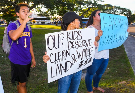 Matthew Santos drinks from a water bottle as his sister, Gilayna Santos, center, protests for clean water as the two stand with Prutehi Litekyan, or Protect Ritidian, members and other grassroot supporters to express their unity in raising awareness of cultural and environmental concerns, regarding the military buildup, during a wave at the Paseo Loop in Hågatña, on Wednesday, July 10, 2019.