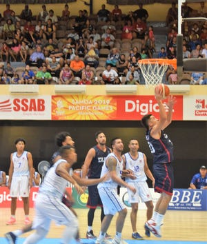 Willie Stinnett takes a baseline feed from Tai Wesley for an easy bucket against Samoa during their Pacific Games opener in Samoa. Guam won 105-81 as it started its gold medal defense.