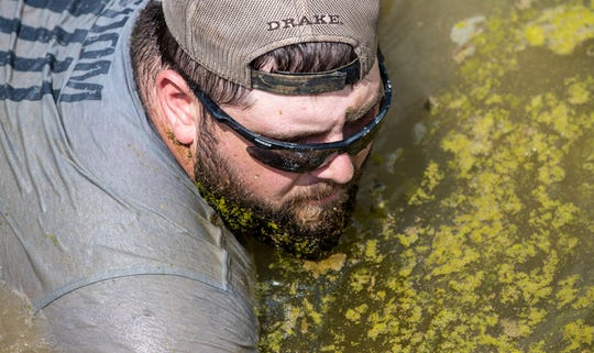 Moss collects in Zac Linne's beard as he swim-crawls in a Dubois County drainage ditch while noodling for snapping turtles on Sunday, July 7, 2019.