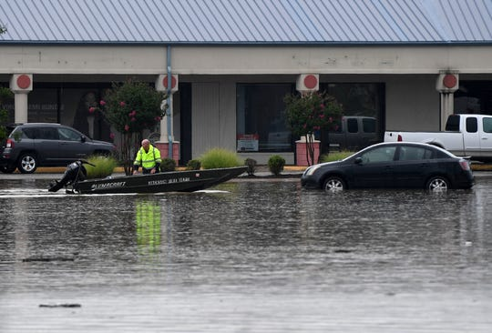 A first responder takes his boat back to dock after rescuing people trapped in their cars in the North Plaza parking lot on the corner of North Highland and Carriage House Dr. after a heavy rain, Wednesday, July 10.
