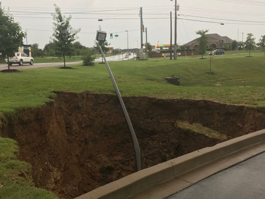 A section of ground caved in near Walker Road behind Academy Sports in north Jackson on July 10 following heavy rains. The cave-in is beginning to spread under the concrete.