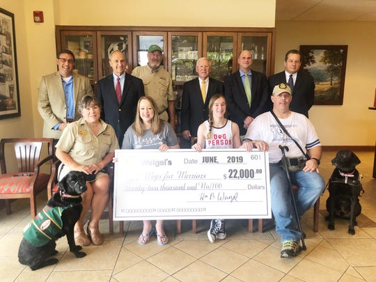 Weigel's presented Smoky Mountain Service Dogs' Wags for Warriors program with a check for $22,000 on July 9, 2019. This is the cost (over a two-year span) to get a dog ready to help a veteran with mobility assistance. The check presentation was held at the Weigel's offices in Powell and pictured are (front): Laurie Brit and Hooligan with Smoky Mountain Service Dogs, Michelle Belcher, Olivia Belcher, veteran Daniel Belcher and Stryker; (back) News Sentinel president Frank Rosamond, Weigel's chairman Bill Weigel, Smoky Mountain Service Dogs spokesperson Mike Kitchens, Weigel's CEO Ken McMullen, director of recruiting for Weigel's Kurt Weigel and Weigel's president Doug Yawberry.