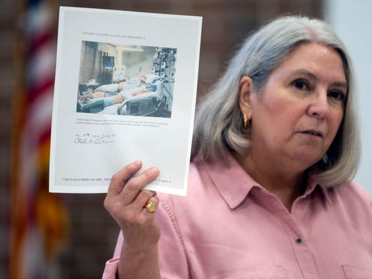 Janie Clark holds up a photograph of a hospitalized Craig Wilkinson during a community meeting for Anderson County residents who are concerned about TVA's plans for its coal ash at Bull Run on July 9. Wilkinson was one of the cleanup workers of the Kingston coal ash spill.