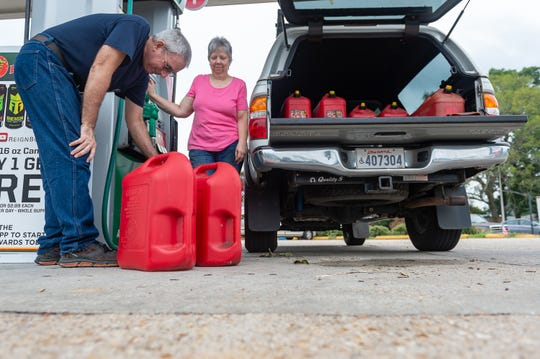 Brett and Tina Delaune fill gas cans Wednesday in preparation for a storm system, forecast to intensify into Hurricane Barry, is predicted to hit the Acadiana area over the next few days.