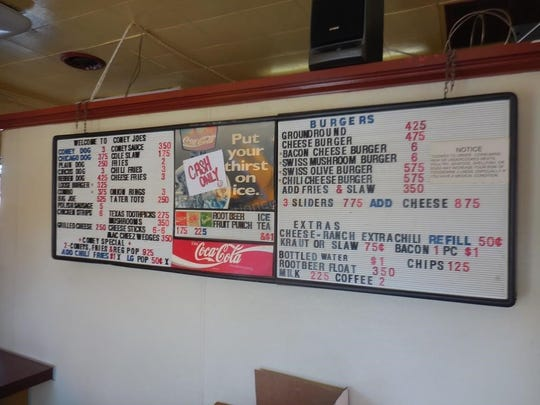 A menu board hangs in the closed Coney Joe's eatery in Brighton. Memorabilia, furnishing and kitchen equipment are up for online auction.