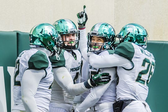 Christopher Laneaux (second from right) celebrated in 2013 with teammates after running back an intercepted pass for a touchdown in the team's Green-White spring football game.