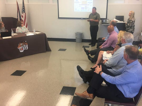 Tim Kissinger of Modern Office Methods discusses printers with members of the Mansfield City School Board during Tuesday's special meeting.