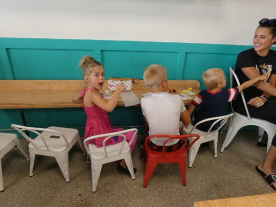 Everleigh Curren, 5, left, and brothers Kingstyn, 8, middle, and Locklan, 3, sit at the kids' bar Tuesday at Topped, a new ice cream shop in Marion.
