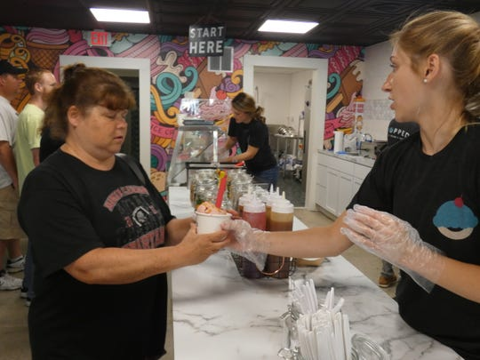 Tammy Adkins, left, orders a strawberry ice cream at Topped, the new ice cream shop at 127 S. Main St. in downtown Marion.