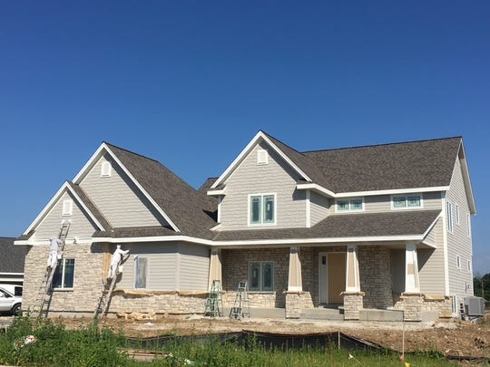 Crews work on a house Wednesday in preparation for next month's annual Parade of Homes. The house is among those being built in the Aero Park subdivision in Menomonee Falls.