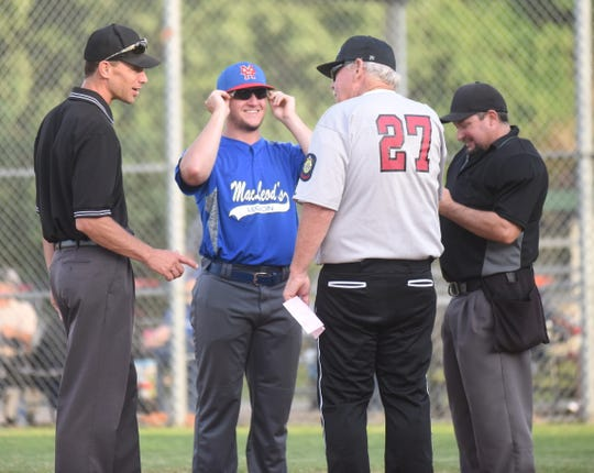 MacLeod coach Brody Ninemire and Lockeroom coach Lester White meet with umpires at the plate before their game earlier this season in the Twin Lakes Classic.