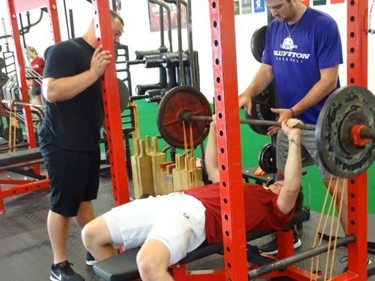 Granville graduate Nate Stone, who will play baseball next spring at Miami, lifts Tuesday morning at Showtime Strength & Performance under the watchful eye of owner Nick Showman, left.