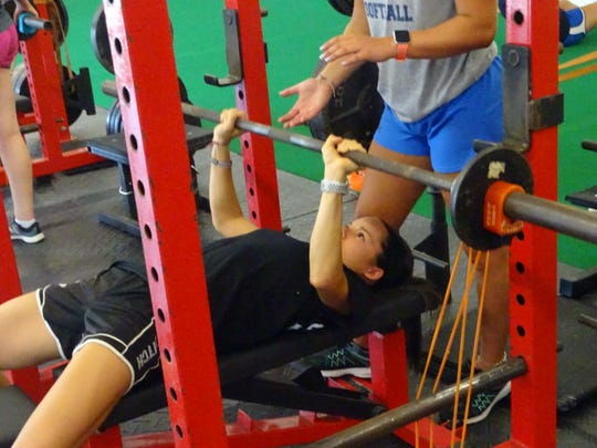 Lakewood graduate Kristin Peacock, a catcher at Lake Erie, lifts Tuesday morning at Showtime Strength & Performance in Newark. Bands are used to increase resistance, which adds acceleration and explosion for the athletes.