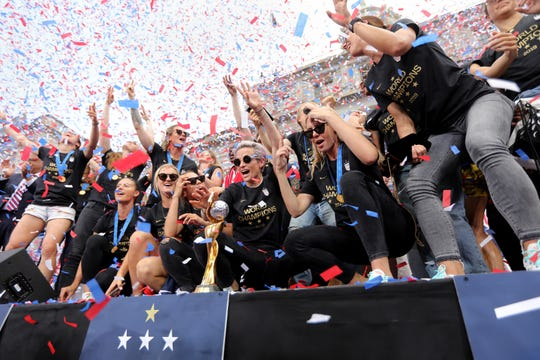 Megan Rapinoe (center, in front of trophy) and the USA National Women's team, celebrate their World Cup victory, at New York City Hall. Wednesday, July 10, 2019