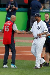 Baseball great Sandy Alomar, left, shakes hands with New York Yankees' CC Sabathia after catching a ceremonial first pitch from Sabathia before the start of the MLB baseball All-Star Game, Tuesday, July 9, 2019, in Cleveland. (AP Photo/Ron Schwane)