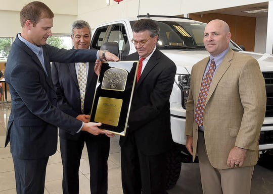 Eric Kinley, far left, Ford Motor Company zone manager, presents Art LeBlanc, Opelousas Sterling Ford owner, with the President's Award while Robert Cook, general manager, and Greg Houston, Ford Motor Company regional manager, looks on. The presentation was made Wednesday.