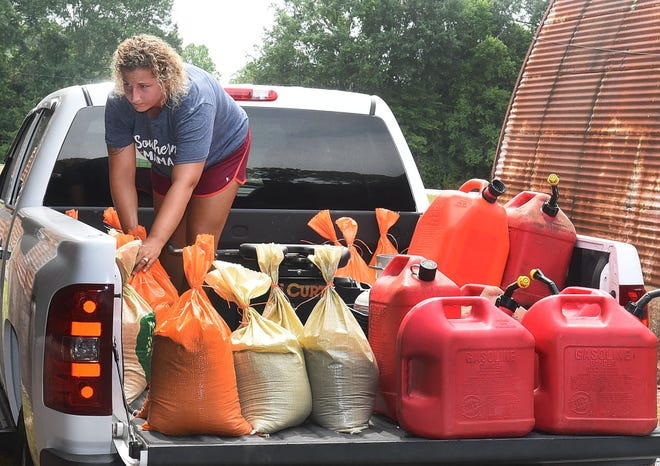 Arnaudville resident, Bridgett Stevens, loads sandbags onto her truck Wednesday ahead of possible flooding in St. Landry Parish from a possible Category 1 hurricane now forming in the Gulf of Mexico. Sandbags are available at the Yambilee Building in Opelousas.