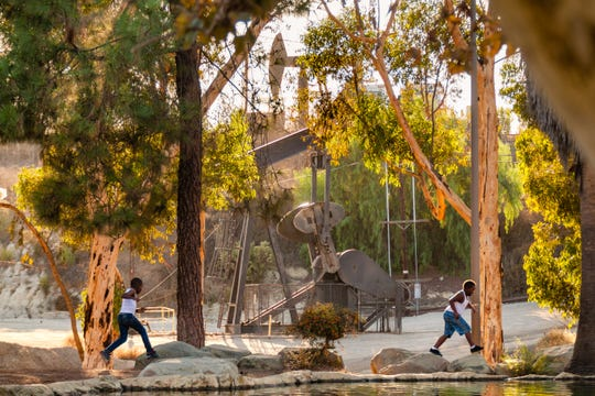 Kids play in Kenneth Hahn State Recreation area near Inglewood, Calif., oil field pump jacks