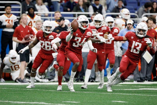 Washington State safety Jalen Thompson (34) celebrates with teammates after intercepting an Iowa State pass during the first half of the Alamo Bowl.
