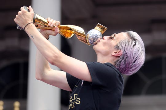 United States women's national soccer team forward Megan Rapinoe (15) celebrates with the trophy at New York City Hall after the ticker-tape parade for the United States women's national soccer team down the canyon of heroes in New York City.