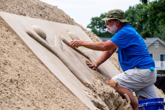 Mark Wilson works Wednesday, July 10, 2019 to carve the a sponsor's logo into the welcome castle for this weekend's Sandfest at the Fort Gratiot Light Station.