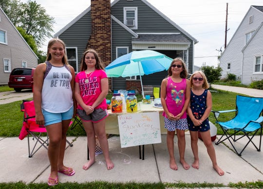 From left, Madison Bezenah, 11; Delanie Tacie, 12, and Kaelyn, 7, and Isabella Bezenah, 9, stand in front of a lemonade stand on the sidewalk in front of the Bezenah's home on 22nd Street Wednesday, July 10, 2019 in Port Huron. The girls came together to hold a lemonade stand to raise money for a family who lost their home in a fire last week.