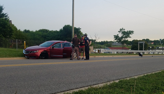 Police stand by a car after it crashed in Port Huron following a police chase.