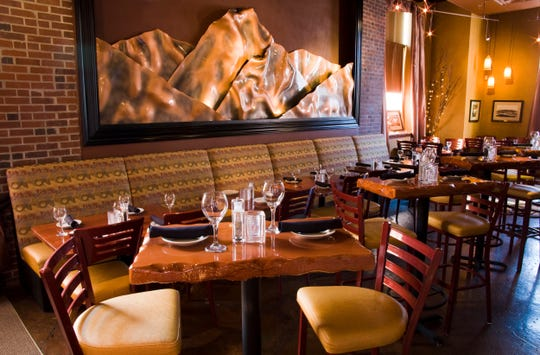 The brick and stone dining room of Wild River Grille features sculpted copper images.