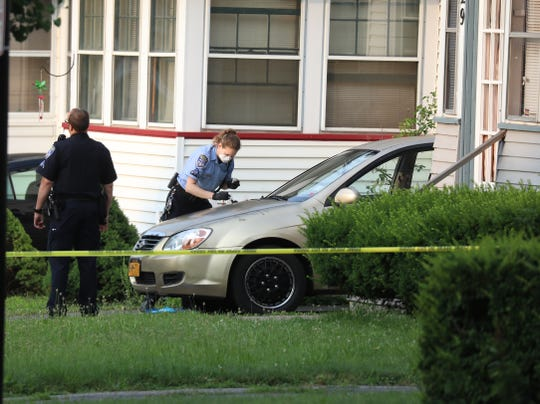 A Rochester Police crime technician dusts a car for fingerprints across the street from the homicide.