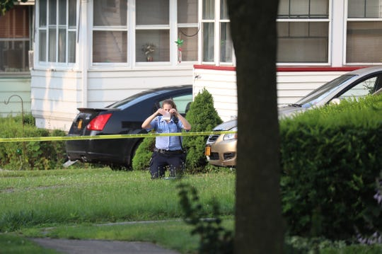 A crime technician bags up evidence from a nearby yard across from the street from where the man was found on Brookdale Ave.