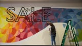 Boz Schurr, a Salem-native artist, works on a 65-foot mural at the Salem Center on July 10, 2019. The mural has a Pacific Northwest team.