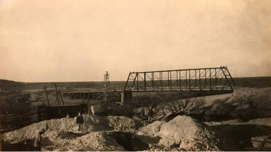 A trestle bridge stands in the background over the South Concho River in this photograph of construction operations at Lake Nasworthy in 1928.