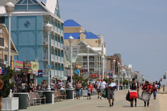 Crowds of tourists and residents walk along the boardwalk in Ocean City on July 10, 2019.