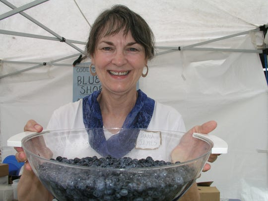 Diana James holds a bowl of blueberries at the blueberry shortcake booth during a past Chincoteague Island Blueberry Festival.