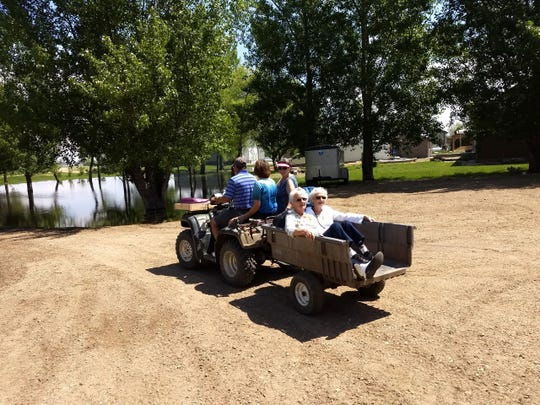 Jim Knight, his sisters, his mother and his aunt all prepare to ride the four-wheeler through flood waters to get to their Lake Preston SD home,which has been surrounded by over two feet of water for the last two months.