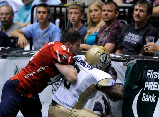 The Storm's Brian McIntire pushes the Tri-Cities Fever's Jason Donnal into the boards Saturday night at the United Bowl IFL championship at the Sioux Falls Arena, June 16, 2011. (Elisha Page/Argus Leader)