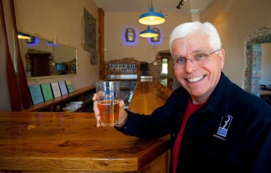 "White River Brewing Company owner John ""Buz"" Hosfield hoists a glass in the new taproom on Tuesday, Oct. 21, 2014. Hosfield died March 26, 2019."