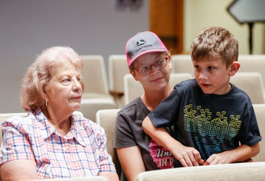 Dana Gray and her son Noah, 8, sit with their neighbor Joen Cook as they talk about a black bear sighting on their properties after a presentation by the Missouri Department of Conservation about Missouri's black bear population on Tuesday, July 10, 2019.