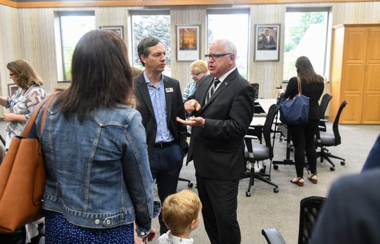 Gov. Tim Walz talks with participants before the start of a roundtable discussion on child care issues in Minnesota Wednesday, July 10, 2019, at the Initiative Foundation in Little Falls.