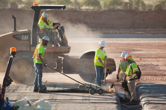 Crews from JP Excavating place a waterproof layer as part of the new runway at the St. George Regional Airport Wednesday, July 10, 2019.