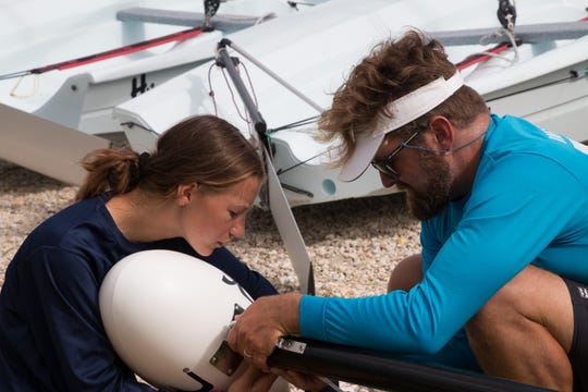 Zuzanna Barska, left, and Nat Osborn install a mast float on top of the Hobie Wave's mast during the Hobie boats assembly volunteer workday  June 29 at the U.S. Sailing Center of Martin County in Jensen Beach.