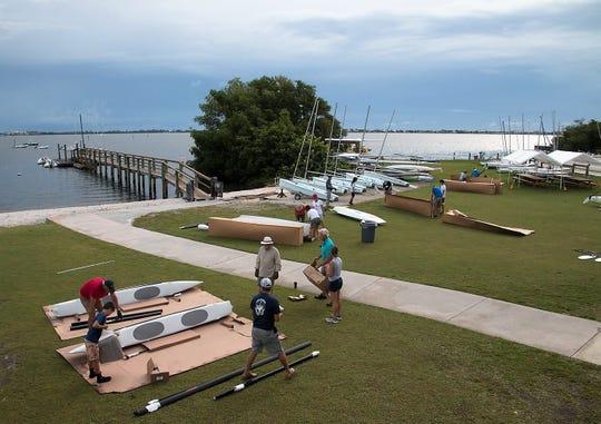 Volunteers begin assembling the new Hobie boats on June 29 at the U.S. Sailing Center of  Martin County in Jensen Beach. A June 13 storm severely damaged seven of 10 Hobie catamarans  owned by the Sailing Center.