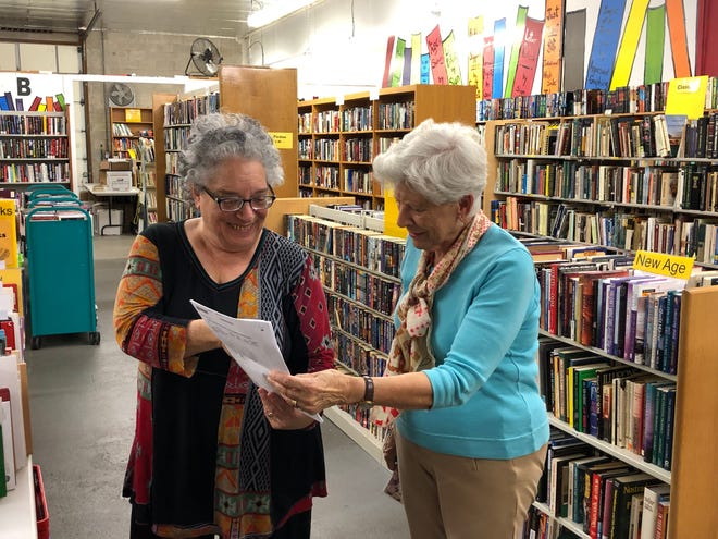Volunteers Sophie Glazer, left, and Edwina Dunworth review a list of authors to assist customers at the Friends' Book Depot in Stuart.