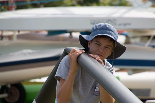 Cameron King discards a bent Hobie mast during the volunteer assembly workday  June 29 at the U.S. Sailing Center of Martin County in Jensen Beach.