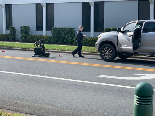 A Vero Beach police officer investigates the crash between a pickup and an electric scooter in downtown Wednesday afternoon.