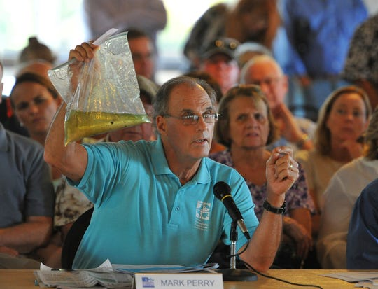 Mark Perry, executive director of the Florida Oceanographic Society in Stuart, shows a sample of algae-laden Indian River Lagoon water during and Aug. 8, 2013, meeting of the Water Resources Advisory Commission at Indian Riverside Park in Jensen Beach.