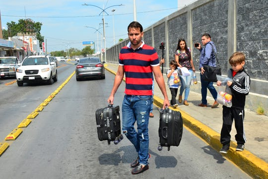 The Ascencio family, from Venezuela, carry their luggage after being returned by U.S. authorities to Nuevo Laredo, Mexico, as part of the first group of migrants to be sent back to Tamaulipas state under the so-called Remain in Mexico program for U.S. asylum seekers on Tuesday, July 9, 2019. Approximately 10 migrants crossed the border Monday to seek U.S. asylum and were sent back on Tuesday to wait as their applications are processed.