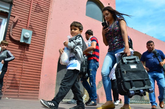 Lucia Ascencio, of Venezuela, carries a suitcase after she and her husband and two sons were returned to Nuevo Laredo, Mexico, as part of the first group of migrants sent back to Mexico's Tamaulipas state under the so-called Remain in Mexico program for U.S. asylum seekers on Tuesday, July 9, 2019. Approximately 10 migrants crossed the border Monday to seek U.S. asylum and were sent back on Tuesday to wait as their applications are processed.